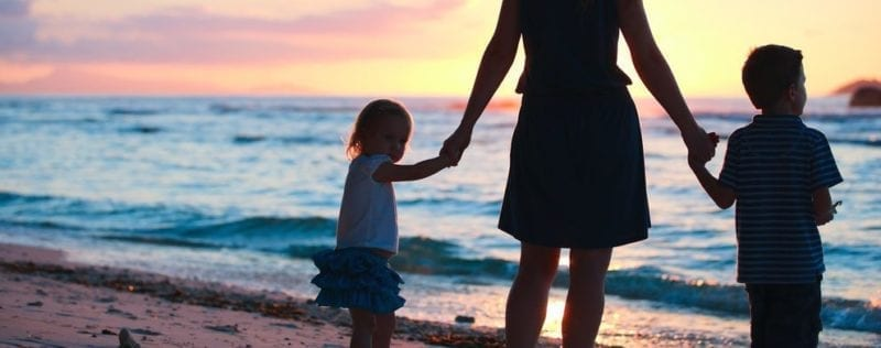 Child Custody FAQ and Answers; woman walking hand in hand with two small children on beach