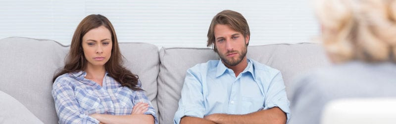 Divorce Mediation; couple sitting on a couch upset talking to mediator