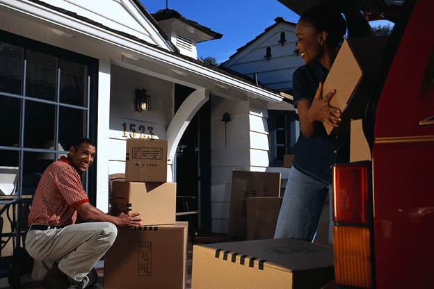 Young black couple loading moving boxes into van