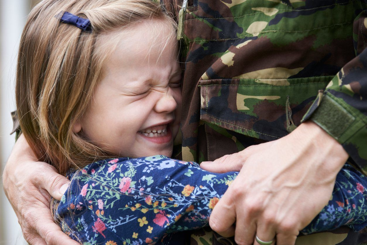 cute little girl tightly hugging man in military uniform - preserving parental rights