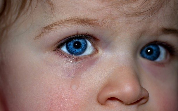 up close baby with blue eyes crying
