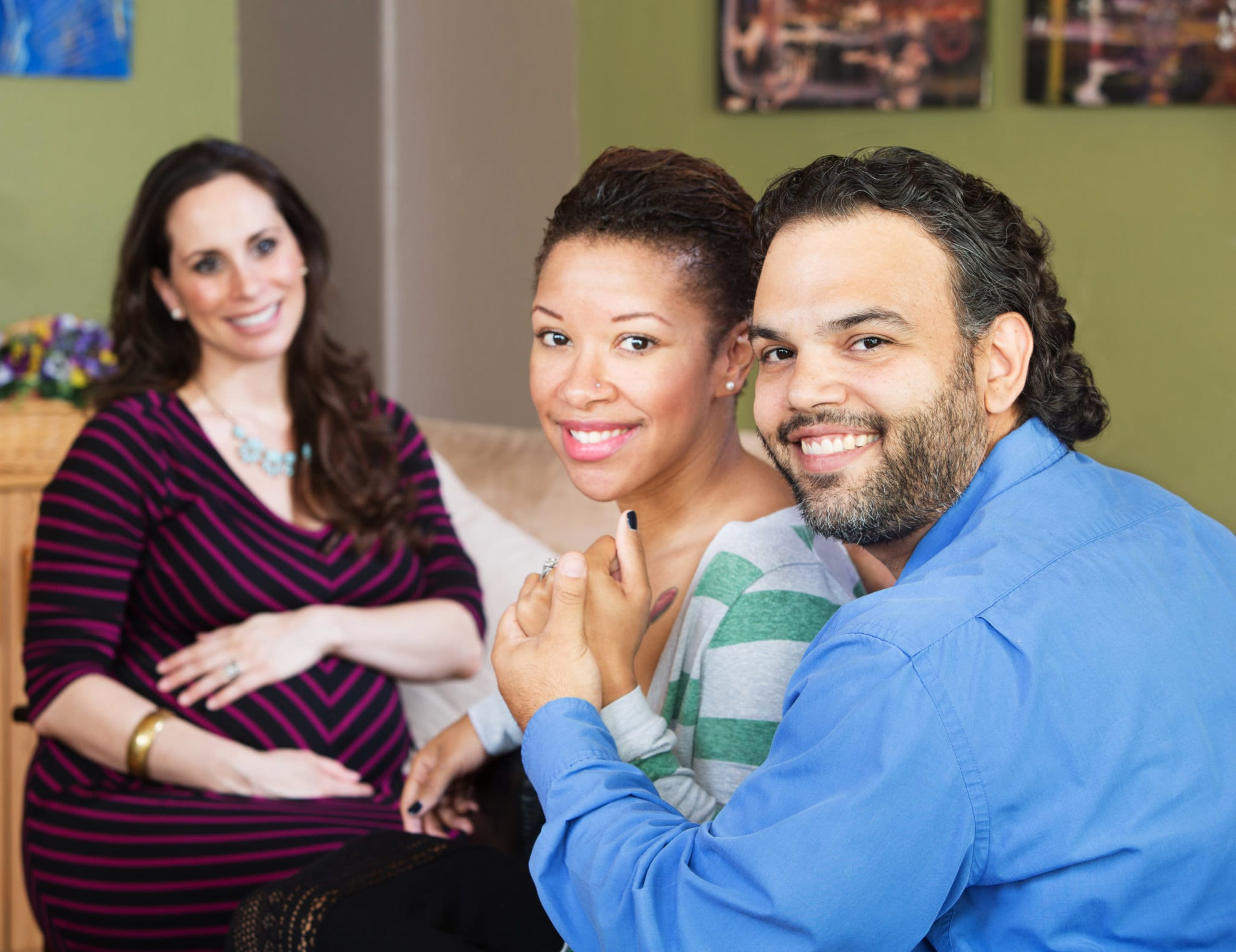 Smiling Hispanic couple sitting with beautiful surrogate mother for IVF